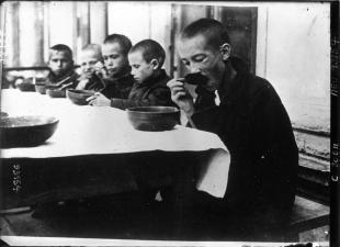 La famine en Russie : dans une cantine, les enfants russes mangent la soupe que l'ARA vient de leur distribuer. Source: Gallica