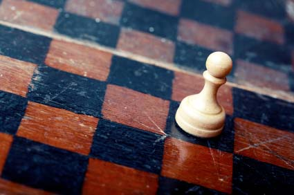 Close-up photo of the old wooden chessboard with white pawn as a symbol of the career.
